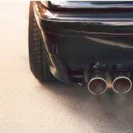 Close-up of black car dual exhaust pipe with smoke